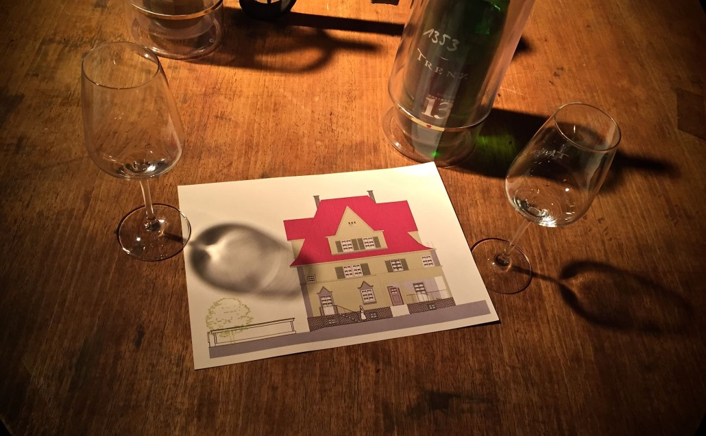 Die Zeichnung einer Jugendstilvilla liegt auf einem Tisch mit Weingläsern und einer Weinflasche.